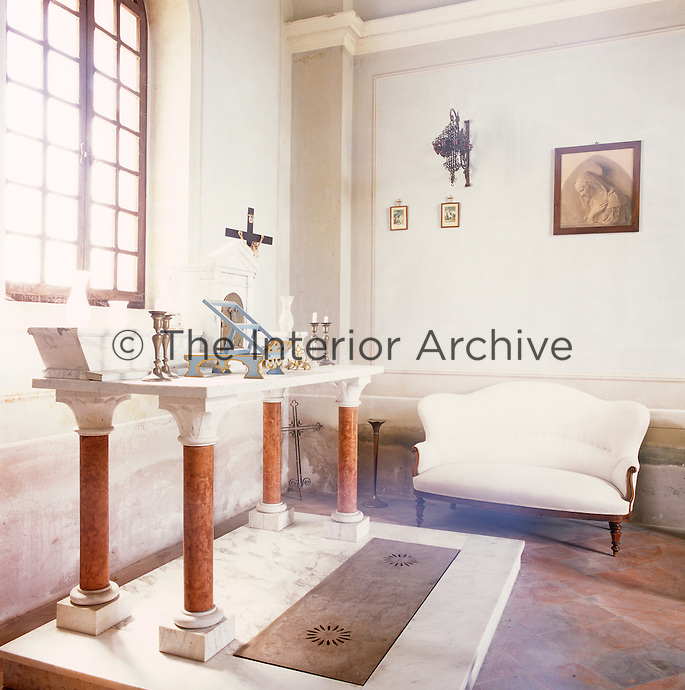 The interior of a former chapel with candlesticks displayed on an altar-like table in front of an arched window. A plain white sofa stands against one wall.