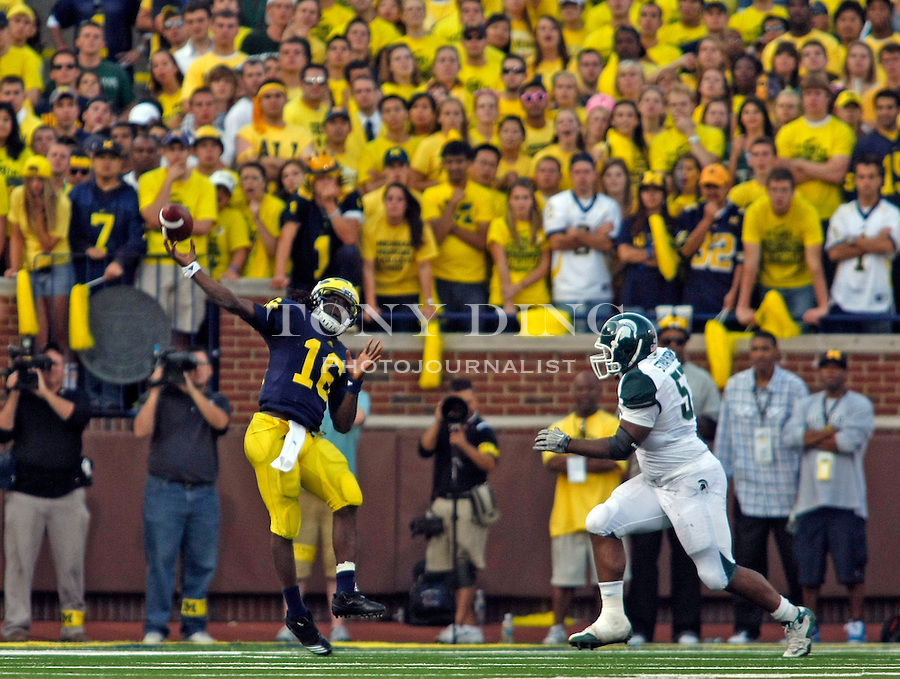 Michigan quarterback Denard Robinson (16) throws an interception in the fourth quarter of an NCAA college football game with Michigan State, Saturday, Oct. 9, 2010, in Ann Arbor. Michigan State won 34-17. (AP Photo/Tony Ding)