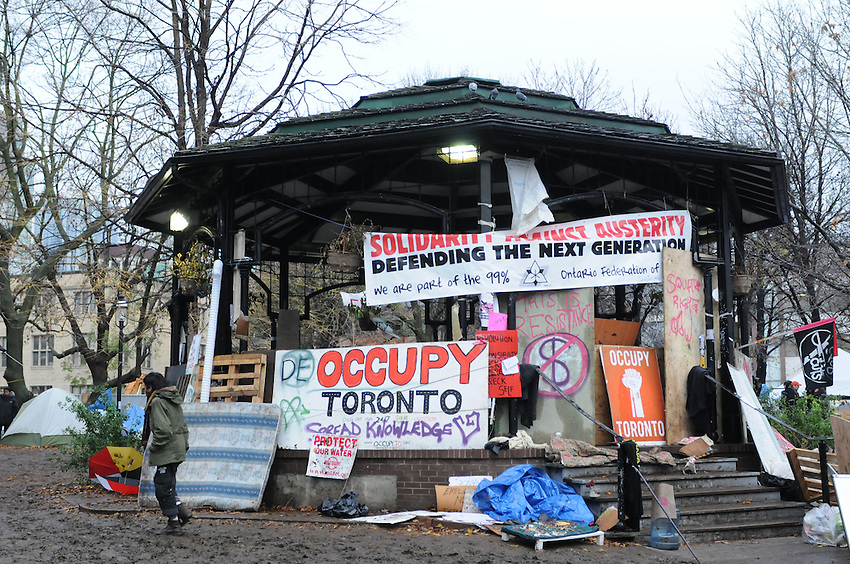 November 23, 2011, Toronto Police and city workers began the process of evicting the Occupy Toronto tent camp from St. James Park and cleaning up.  Here, a lone unidentified protest supporter passes by the barricaded park band shell.