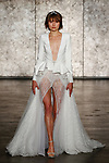 Model walks runway in a peplum deep v coat dress with fully sequined front slit tulle ballerina skirt, from Inbal Dror Fall 2018 bridal collection on October 5, 2017; during New York Bridal Fashion Week.