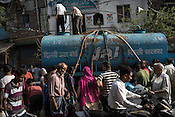 Commuters walk past the residents gathered to collect water from a Delhi Jal Board water tanker in the slums of Govind Puri in New Delhi, India. Photo: Sanjit Das for The Foreign Policy