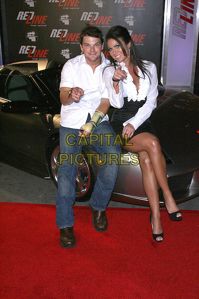 "NATHAN PHILLIPS & NADIA BJORLIN .""Redline"" The Movie Presents Wyclef Jean & The Refugee All-Stars Sponsored by MySpace.com held at The House of Blues on Sunset, Los Angeles, California, USA..February 12th, 2007.full length white ruffle blouse black skirt jeans denim pointing sitting car.CAP/ADM/ZL.©Zach Lipp/AdMedia/Capital Pictures"