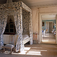 To the left of the canopied bed in the sunlit master bedroom stands an 18th century dolls' house