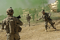 Baqubah, Iraq, March 31, 2007 - <br /> <br /> U.S. Army Sgt. Bill Stachler throws a smoke grenade to mask his team's movements during a joint operation with the Iraqi police in Baqubah, Iraq, March 31, 2007. The purpose of the operation is to clear houses and palm groves near the Diyala River of any insurgent forces.  Stachler is with the 5th Battalion, 20th Infantry Regiment. (U.S. Air Force photo by Staff Sgt. Stacy L. Pearsall) (Released)