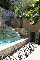 The medieval origins of this simple village house contrast with the contemporary structure and texture of the new stone wall that encloses the outdoor swimming pool