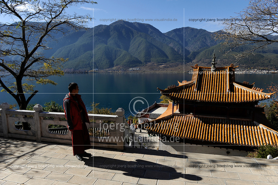 CHINA Province Yunnan Lugu Lake , ethnic minority Mosuo who are buddhist and women have a matriarch, buddhist temple on island in the Lake, buddhist monk / CHINA Provinz Yunnan , ethnische Minderheit Mosuo am Lugu See , die Mosuo sind Buddhisten und Mosuo Frauen ueben ein Matriarchat aus, buddhistische Pagode auf Insel im See