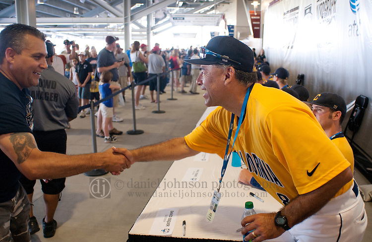 17 June 2011  -- David Esquer California Berkeley Baseball. University of California Berkeley baseball coach David Esquer, right, shakes the hand of a fan during opening day celebrations on Friday, June 17 at TD Ameritrade Park Omaha for the College World Series in Omaha, Nebraska. PHOTO/Daniel Johnson (Copyright 2011 Daniel Johnson)