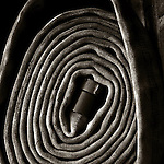 Rolled fire hose in sepia.