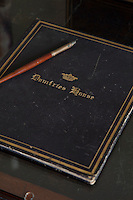 A leather notebook, or possibly blotting pad, embossed with the name of the house