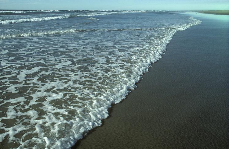 Gentle breaking waves on a sandy beach in the UK