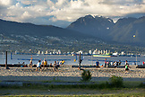 CANADA, Vancouver, British Columbia, looking over the Straight of Georgia towards West Vancouver and Brunswick Mountain from Spanish Banks Beach Park, people playing volleyball in the foreground
