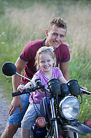 Polish teen boy motorcyclist giving ride to excited neighbor girl age 18 and 5. Zawady Central Poland
