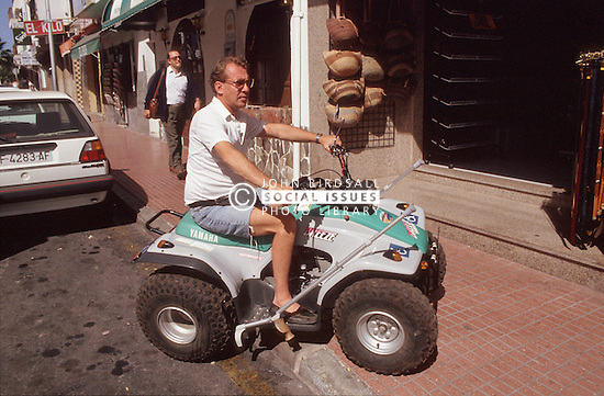 Man with disability riding quad bike; climbing pavement,