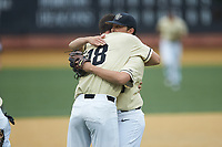 Wake Forest Demon Deacons senior pitcher Ben Casstevens (20) gets a hug from Carter Bach (18) as he walks off the field during the game against the Miami Hurricanes at David F. Couch Ballpark on May 11, 2019 in  Winston-Salem, North Carolina. The Hurricanes defeated the Demon Deacons 8-4. (Brian Westerholt/Four Seam Images)