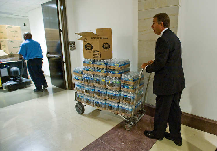 House Minority Leader John Boehner, R-Ohio,  gives a little help to a AOC worker moving bottled water. Boehner was on his way back to his office after the stake out for the House Republican Conference in the U.S. Capitol, September 23, 2009..