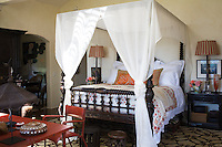 The master bedroom is furnished with a large 19th century colonial four-poster bed found in a palace in Rajasthan