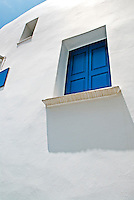 The labyrinthine of alleyways on the Greek island of Mykonos are lined with cube-shaped whitewashed houses and churches that wind uphill on streets of cobbled pavements.