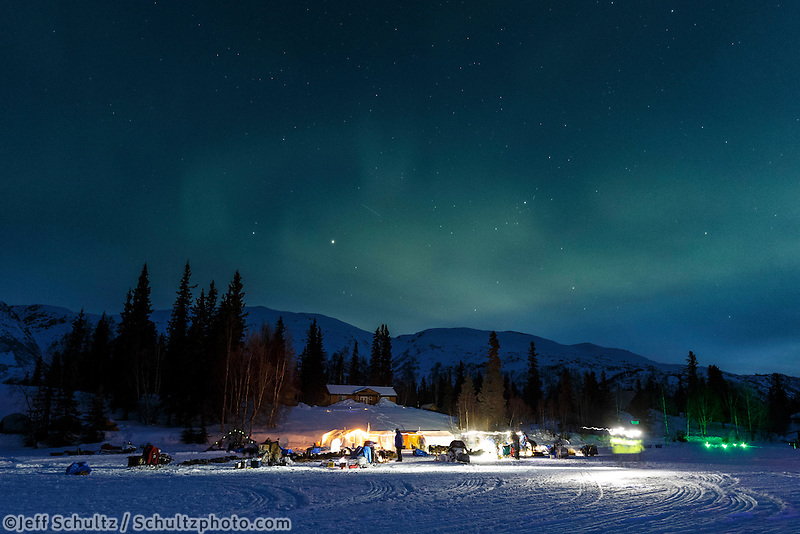 The northern lights light up the sky over resting dog teams in the early morning at the Finger Lake checkpoint at Winterlake Lodge during Iditarod 2016.  Alaska.  March 07, 2016.  <br /> <br /> Photo by Jeff Schultz (C) 2016 ALL RIGHTS RESERVED