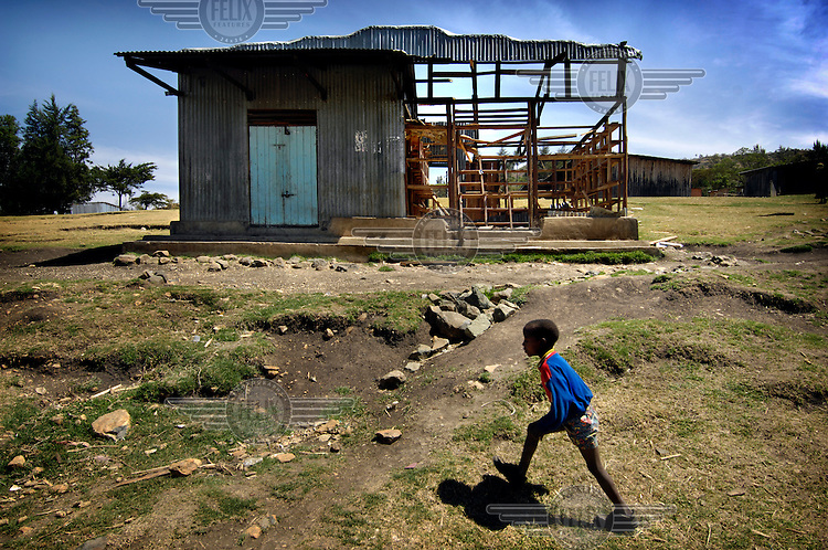 Small boy walks past a partially destroyed house. The right half belonged to a Kikuyu and was therefore destroyed. The left is owned by a Kalenjin and remained intact. Ethnic violence sparked last December following protests against disputed election results, after suspected vote rigging by Kikuyu President Mwai Kibaki.
