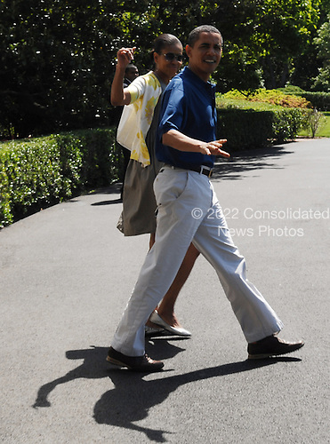 Washington, DC - May 23, 2009 -- United States President Barack Obama and first lady Michelle Obama walk out of the White House toward Marine One in Washington on Saturday, May 23, 2009. The President is traveling to Camp David for Memorial Day weekend. .Credit: Alexis C. Glenn / Pool via CNP