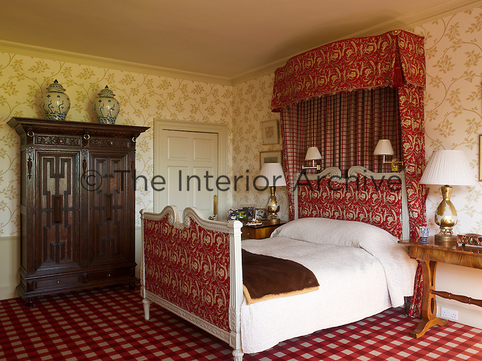 This bedroom is furnished with a French bed with red and white patterned fabric, a checked carpet and an antique Dutch wardrobe