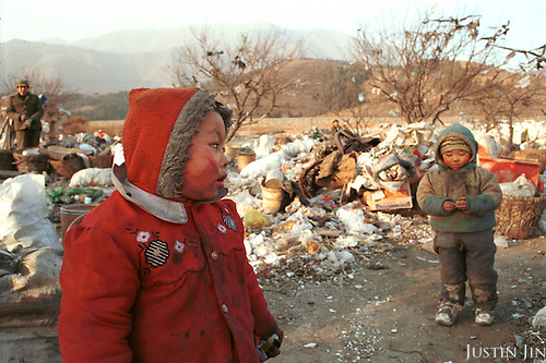 Sichanese kids stand around in freezing cold at the Beijing garbage dump. They have no right to go to local schools in the capital, which faces big problems with the constant influx of rural migrants. ..Experts estimate that about 40 million rural workers roam Chinese cities looking for jobs, bringing with them a further 30 million spouses and children...Picture taken December 1997.Copyright Justin Jin
