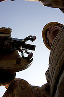 an Iraqi tanker gunner from the 1st company, 1st armour battalion of the 1st mechanized Iraqi Army Brigade  rides in his tank while conducting  patrols, check points and observation posts on code name route Michigan, the main road of Ramadi in the week during the national election on TUE Dec 13 2005 in Ramadi, Iraq. 1st company is part of the first armor battalion of the New Iraqi Army. it has started its training in January 2005. after 50 days their 35 russian and chinese built T 55 tanks begun conducting operations under the guidance of a US military adivisor team. in April 2005 they patrolled in the Abu Ghraib area concluding their first significant mission. While these old tanks are rolling on the ramadi streets more modern T72s are getting ready to become fully operational in Taji, their main base. the Iraqi army wanted to show their power in ramadi during the Dec 15 elections displaying their new armour company. but like all the other Iraqi forces they are not going to secure the polling sites, staying in the rear with the rest of the iraqi and coalition forces. T 55s are very old tanks. production begun in the late 50s to the late 70s. athough obsolete many countries still use the T55 as their main heavy armoured combat vehicle. slow, heavvy and with very little room for the crew it suffers from many mechanical problems constantly challenging the iraqi mechanics and engineers.
