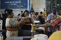 Lady fish sellers drops their tips for the street band while they are playing to sellers and shoppers in the Central Market of Paramaribo. This is a tradition in Suriname and the bands plays at different locations, places before  important days, festive start.....End of year 2010 celebrations on the streets of Paramaribo. Suriname is one of biggest consumer in South America that using firecrackers, fireworks ( also locally known as pagara ) for celebrations, especially for end of every years and also beginning of every new Chinese Years.
