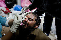 An anti-government protester is treated for injuries to his eye sustained in violent clashes with pro-Mubarak supporters in a mosque that is acting as an emergency hospital just off Tahrir Square. Continued anti-government protests take place in Cairo calling for President Mubarak to stand down. After dissolving the government, Mubarak still refuses to step down from power.