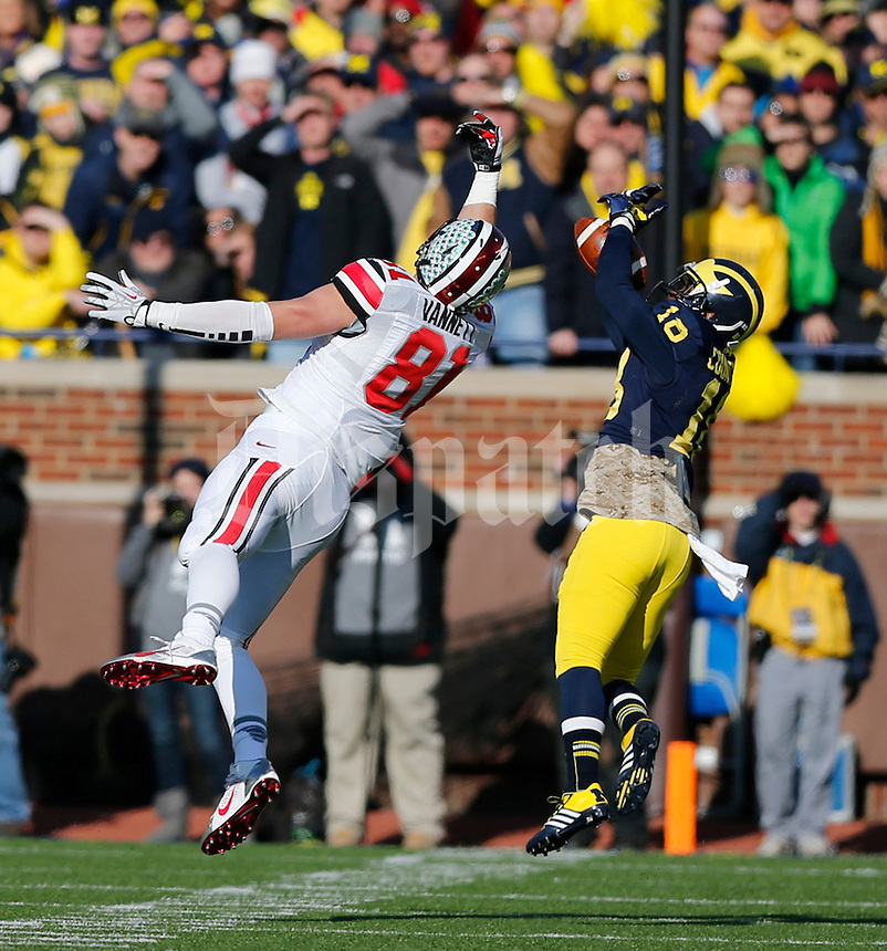 Michigan Wolverines defensive back Blake Countess (18) gets an interception against Ohio State Buckeyes tight end Nick Vannett (81) during the first half of the NCAA football game at Michigan Stadium in Ann Arbor, Michigan on Saturday, November 30, 2013. (Columbus Dispatch photo by Jonathan Quilter)