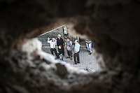 Syrian civilians are seen through a hole made by bomb explosion as they watch up one army helicopter flying the sky and shooting the by side neighborhood. The Hospital located at the northeast area of the City was targeted four times by aircraft shelling, depite the bombing the Hospital still operating and giving medical care to the civilian population.