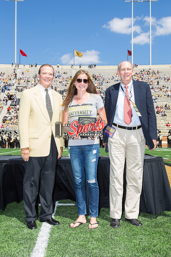 Bea Bielik (center) receives her Wake Forest Hall of Fame plaque from Athletic Director Ron Wellman (left) and Dr. Richard Carmichael (right) at half-time of the football game against the Louisiana-Monroe Warhawks at BB&T Field on September 14, 2012 in Winston-Salem, North Carolina.    (Brian Westerholt/Sports On Film)