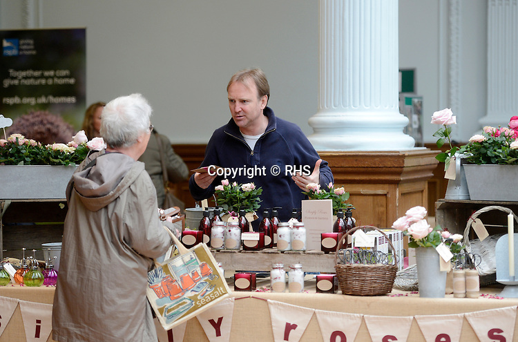 A visitor talks to an exhibitor on the Simply Roses stand at an RHS Secret Garden Sunday.