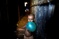 A child poses with a ball in the Mirpur slum in Dhaka.