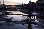 QUEENS, NY -- OCTOBER 22, 2013:  A cyclist maneuvers the potholes on Willets Point Blvd in Willets Point on October 22, 2013 in Queens.  Photographer: Michael Nagle for The New York Times