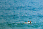 Two men in small raft in large expanse of water