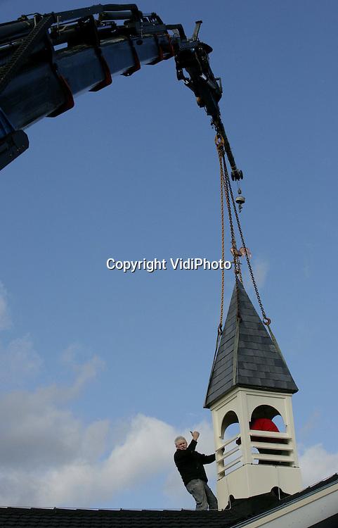 Foto: VidiPhoto..EDE - Terwijl door heel Nederland kerken worden gesloopt, springen ze op de Veluwe als paddestoelen uit de grond. Een van de oorzaken is de scheuring van de Nederlandse Hervormde Kerk enkele jaren geleden, waardoor diverse gemeenten op dit moment zelf een kerkgebouw neerzetten. Dinsdag is de toren op het kerkje van de Hersteld Hervormde gemeente van Ede-Bennekom gehesen. De verbouwde showroom is geschikt gemaakt voor 450 kerkgangers en wordt op 6 april officieel in gebruik genomen. Het gebouw is in een jaar tijd vrijwel geheel door vrijwilligers verbouwd als kerk. Woensdag wijst de rechter vonnis in de slepende kerkruzie tussen de PKN en de Hersteld Hervormde Kerk die zichzelf de juridische eigenaar vindt van alle bezittingen van de Nederlandse Hervormde Kerk (nu PKN). Begeleidende aannemers zijn Methorst uit Renkum, Van Engelenhoven uit Ede en Zondag Bouwadvies uit Ede.