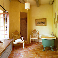 The yellow bathroom is sparsely furnished with a green roll-top bath and a pair of Louis XIV cane-backed chairs