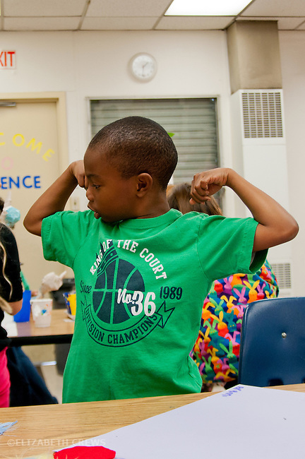 Berkeley CA 1st grade African American boy showing off muscles in class