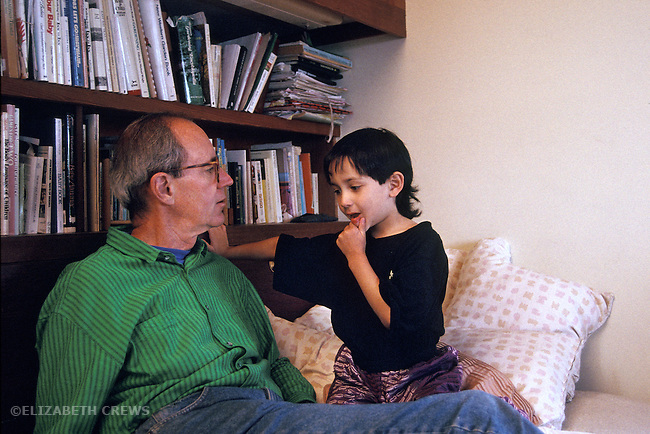 Berkeley CA  Boy, five-years-old, in serious conversation with grandfather at home