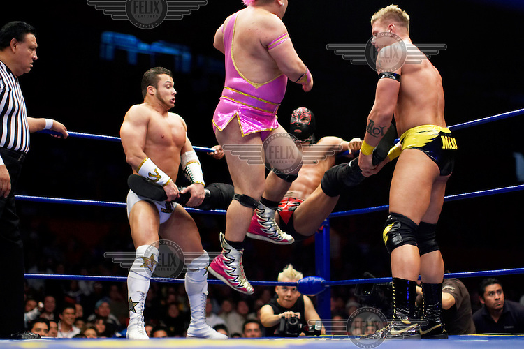 A Luchador (fighter) named Geronimo (in pink), who plays the part of a homosexual, jumps to kick another wrestler. Lucha Libre is a style of wrestling started in Mexico in 1933. The name means Free Fight, and matches tend to be focussed on spectacle and theatre with fans cheering for their favourite characters, who wear masks while jumping from the ropes, flipping opponents, and occasionally crashing into the crowd..