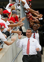 Ohio State Buckeyes head coach Urban Meyer high fives ushers as he walks into the stadium prior to the NCAA football game against Northern Illinois at Ohio Stadium in Columbus on Sept. 19, 2015. (Adam Cairns / The Columbus Dispatch)