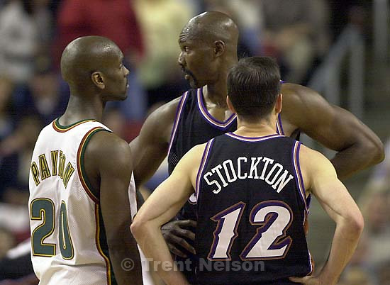 Gary Payton mockingly stands in on a huddle between Karl Malone and John Stockton at Jazz vs. Sonics, game 4, 1st round NBA playoffs. Sonics won.<br />