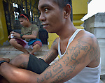 "Tattoos on the arm of a young man in the Manila North Cemetery. Hundreds of poor families live here, dwelling in and between the tombs and mausoleums of the city's wealthy. They are often discriminated against, and many of their children don't go to school because they're too hungry to study and they're often called ""vampires"" by their classmates. With support from United Methodist Women, KKFI provides classroom education and meals to kids from the cemetery at a nearby United Methodist Church."