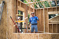 NWA Democrat-Gazette/CHARLIE KAIJO Dennis Kronberg of Wausa, Neb. (center) installs refrigeration lines for air conditioning, Friday, June 8, 2018 on Passion Play Road, across the street from the Washington Regional clinic in Eureka Springs. <br /><br />Eight tiny houses are being built in Eureka Springs, which has a dearth of affordable housing. They're being constructed by 66 volunteers from 13 states with World Mission Builders. They began work on Monday (June 4) and should finish most of the construction by the end of next week (June 15). Then local volunteers will finish out the interiors and put shingles on the roofs. The first eight houses are part of what will be called ECHO Village. Plans are to eventually have 26 houses in the village. It's a project of Eureka Christian Health Outreach, which bought 10 acres for the village. The same group started ECHO Clinic in Eureka Springs in 2005. It provides free medical care to the uninsured and people on a low income.