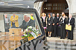Con Houlihan ashes are placed in the hearse by Joe Tangney as his family watch on Friday