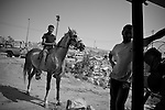 A Palestinian youth sits upon his horse alongside a scrap metal merchant from Al Khalil (Hebron) in  Al 'Eizariya (Bethany) near Jerusalem on 03/06/2010.