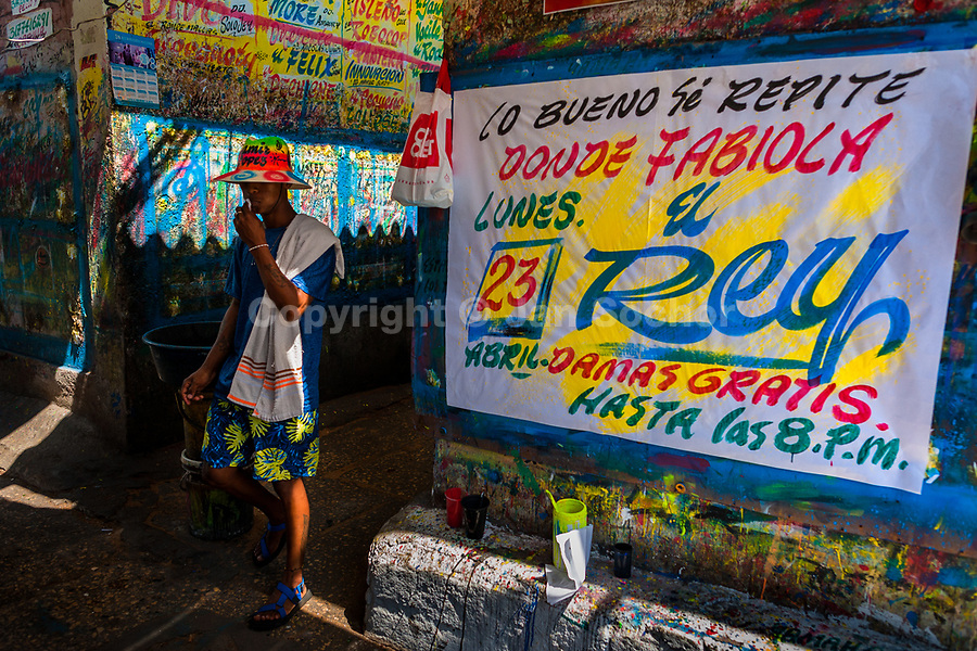 """A Colombian sign painter walks along a just-finished music party poster in the sign painting workshop in Cartagena, Colombia, 14 April 2018. Hidden in the dark, narrow alleys of Bazurto market, a group of dozen young men gathered around José Corredor (""""Runner""""), the master painter, produce every day hundreds of hand-painted posters. Although the vast majority of the production is designed for a cheap visual promotion of popular Champeta music parties, held every weekend around the city, Runner and his apprentices also create other graphic design artworks, based on brush lettering technique. Using simple brushes and bright paints, the artisanal workshop keeps the traditional sign painting art alive."""