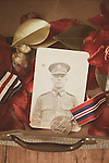 Flowers, photographs and medals in and old suitcase