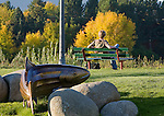A bronze fish sculpture and a man on a park bench along the Clark Fork riverfront trail in Missoula, Montana